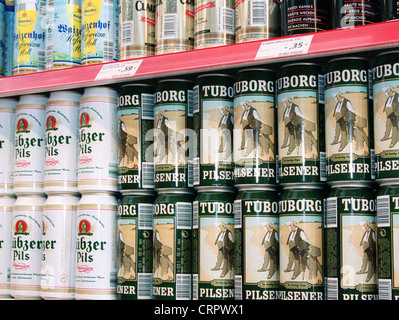 Beer cans in a supermarket shelf. - Stock Photo