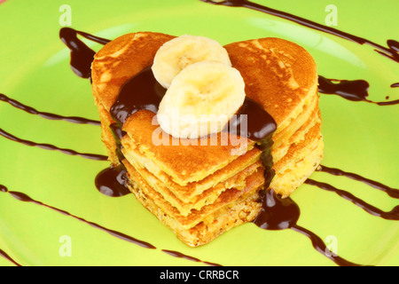 Heart shaped pancakes with chocolate sauce and banana slices on a green dish. A perfect breakfast for Valentine's - Stock Photo
