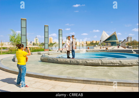 Chinese girls take photographs of each other in Donghu Park with the pavillion behind in Kashgar. - Stock Photo