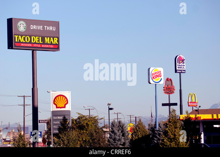 Giant signs advertising fast food chain restaurants tower above highway in Ellensburg Washington State USA - Stock Photo