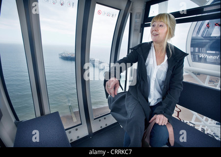 The Brighton Eye Ferris Wheel on Brighton seafront. A woman sightseer in one of the pods overlooking the beach and - Stock Photo