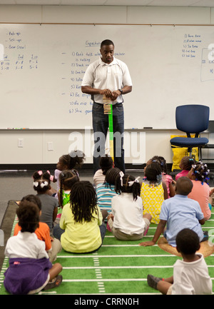 African-American male kindergarten teacher in class with students head start program at public charter in Texas - Stock Photo