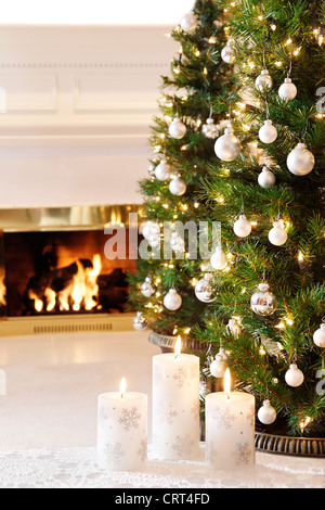 Snowflake candles and glittering decorations by a warm fire - Stock Photo