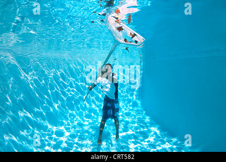 Young man is cleaning the swimming pool from underwater with a skimmer net - Stock Photo