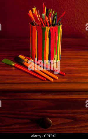Still Life paint brushes in paint can on desk - Stock Photo