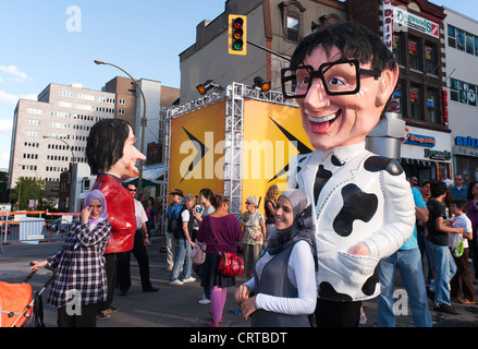 Giant headed papier mâché characters strolling on Ste-Catherine street during the Just for Laughs Festival in Montreal, - Stock Photo
