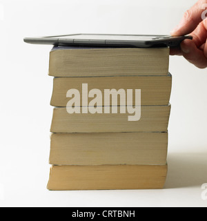 Electronic book on top of a pile of paperbacks - Stock Photo
