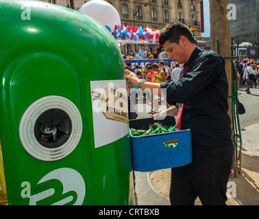 Paris, France, French Café Waiter Recycling Glass Bottles into Street Container - Stock Photo