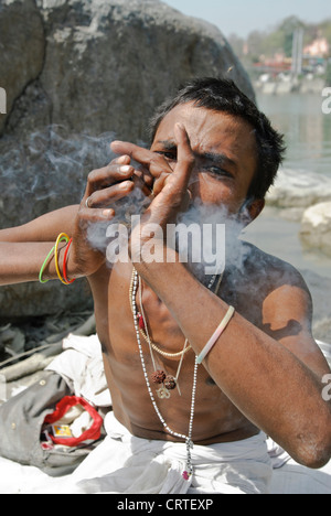 An Indian Sadhu smokes hashish from a pipe next to the River Ganges in Rishikesh, India. - Stock Photo
