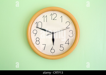 Clock hanging on wall and showing current time - Stock Photo