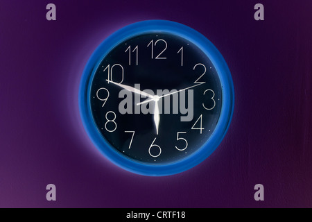 Shaded clock hanging on wall and showing time - Stock Photo