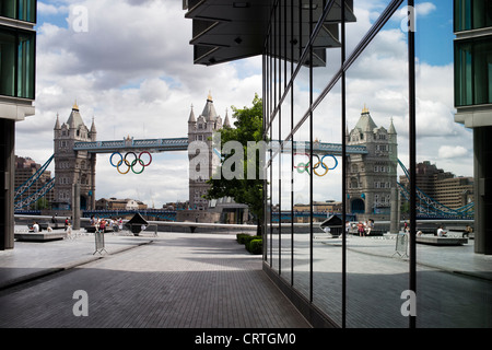 Tower bridge and the 2012 Olympic Rings reflected in glass windows. More London Riverside. England - Stock Photo