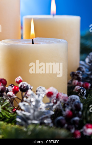 Three burning candles in an advent flower arrangement for advent and Christmas a nice close up shoot - Stock Photo