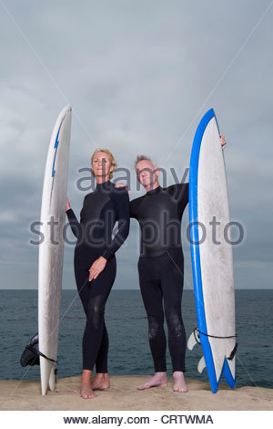 Male and female surfers in wetsuits with surfboards by beach - Stock Photo
