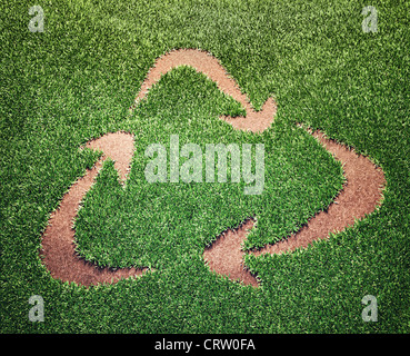 Recycling symbol in a field of grass - Stock Photo