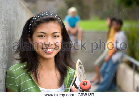 Teenage girl (13-15) with skateboard by friends outdoors, smiling, portrait - Stock Photo