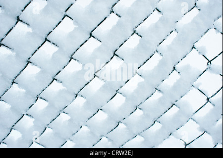 snow on a chain link fence - Stock Photo