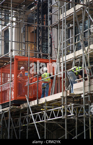 Construction workers on scaffolding in City of London - Stock Photo