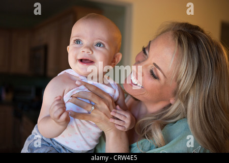 Happy mother smiling at her happy one year old at home. - Stock Photo