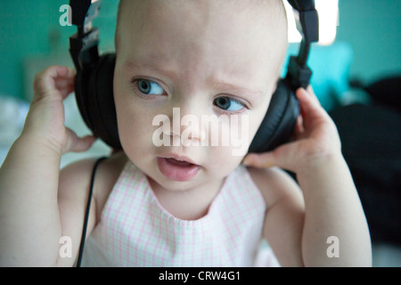 One year old listening intently to sound on headphones, closeup.