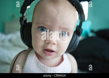One year old girl wearing large headphones and looking wide-eyed. - Stock Photo