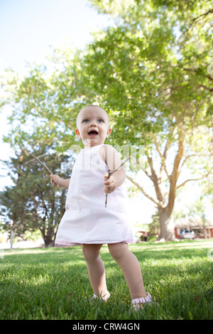 A happy one year old girl looks up, holding sticks in her hands in a park. - Stock Photo