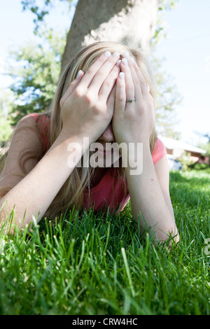 Humiliated thirteen year old girl covers her face with her hands outdoors. - Stock Photo