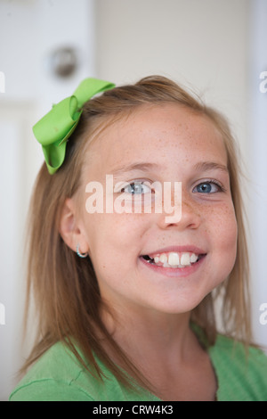 Happy nine year old girl swmiling wearing a green ribbon. - Stock Photo