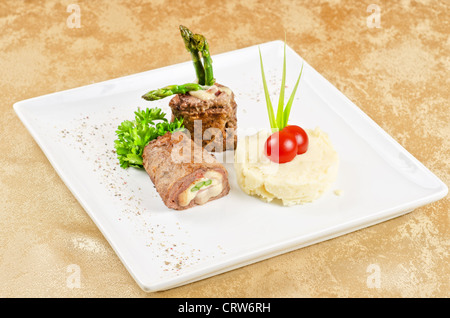Grilled meat rolls from beef meat with mozzarella, ham, asparagus and mashed potatoes - Stock Photo