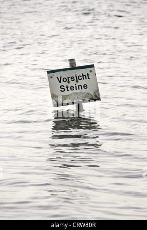 Caution sign stones on the beach - Stock Photo