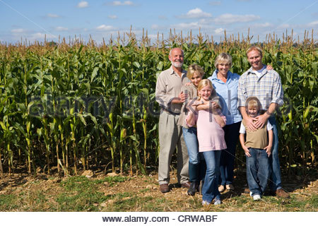 Family of three generations by corn field, smiling, portrait - Stock Photo