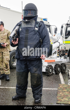 ATO Soldier from 321 EOD Squadron in a bomb-proof suit and carrying a controlled explosion charge (pigstick) - Stock Photo