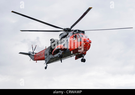 Royal Navy Sea King helicopter Rescue 177 in flight - Stock Photo