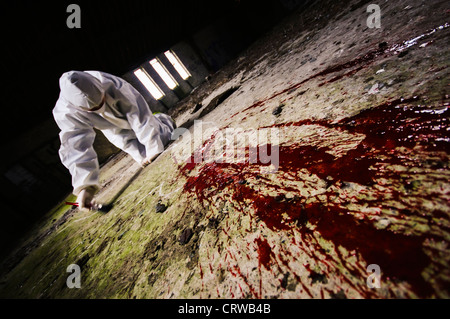 Scene of Crime Officer in a boilersuit (SoCO) gathering evidence at a murder scene - Stock Photo
