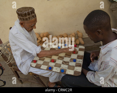 Elderly Muslim man play draughts with young African man in the old town in Mombasa, Kenya - Stock Photo