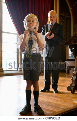 Boy (5-7) with trophy, man clapping by lectern in background - Stock Photo