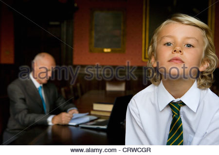 Boy (5-7) in office with father at desk in background - Stock Photo