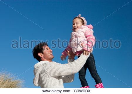Father lifting daughter against sunny, blue sky - Stock Photo