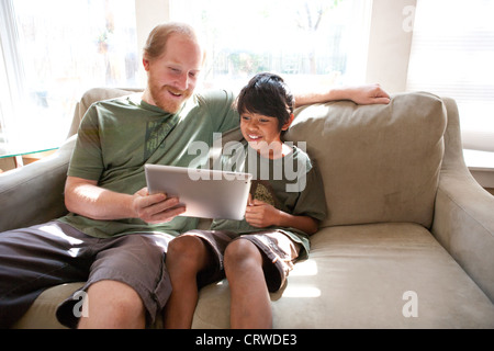 Father and adopted ten year old son watch a funny video on an Ipad at home. - Stock Photo