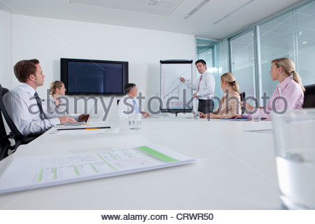 Businessman standing at chart and leading meeting in conference room - Stock Photo