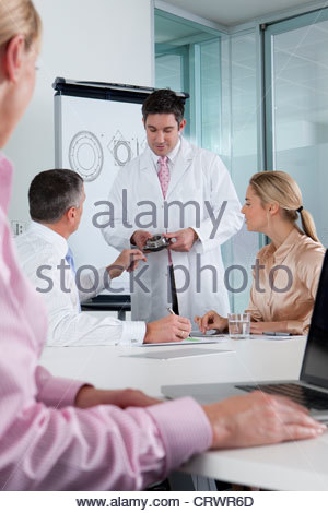 Engineer explaining machine part to business people in conference room - Stock Photo