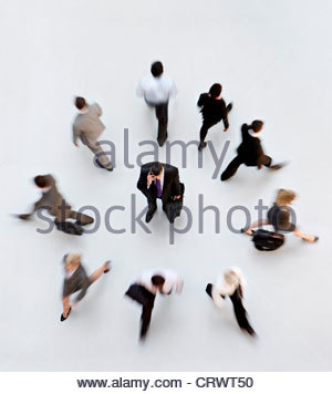 Business people walking away from businessman talking on cell phone - Stock Photo