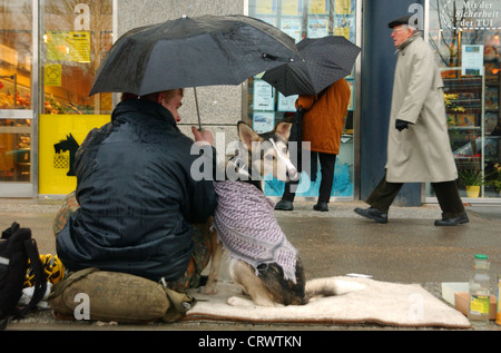 Homeless man with his dog in Berlin - Stock Photo