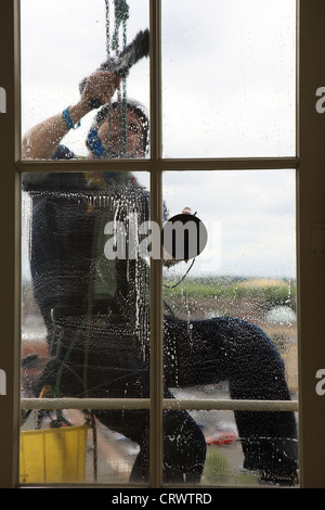 Abseiler window cleaner on the outside of the building - Stock Photo