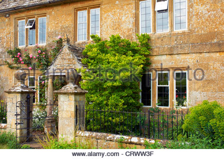 traditional stone cottage with pink roses around front door and windows in great rissington in the cotswolds gloucestershire - Stock Photo