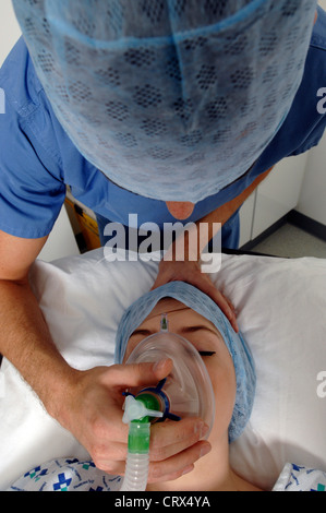 An anaesthetist administering medical gases to put a patient to sleep at the start of an operation. - Stock Photo