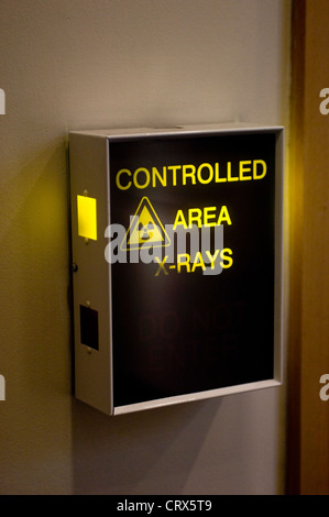 An illuminated hospital sign outside a controlled area for x-rays - Stock Photo