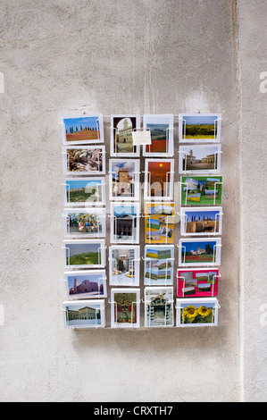 Picture post cards in a rack on the wall outside of a shop in Italy - Stock Photo