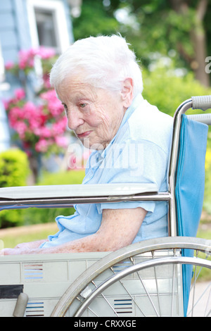 Senior lady in wheel chair in front of house with pink flowers - Stock Photo