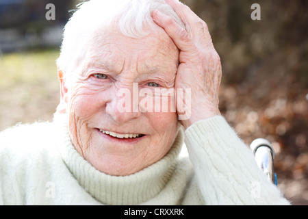 Happy Elderly Woman in Wheelchair Smiling - Stock Photo